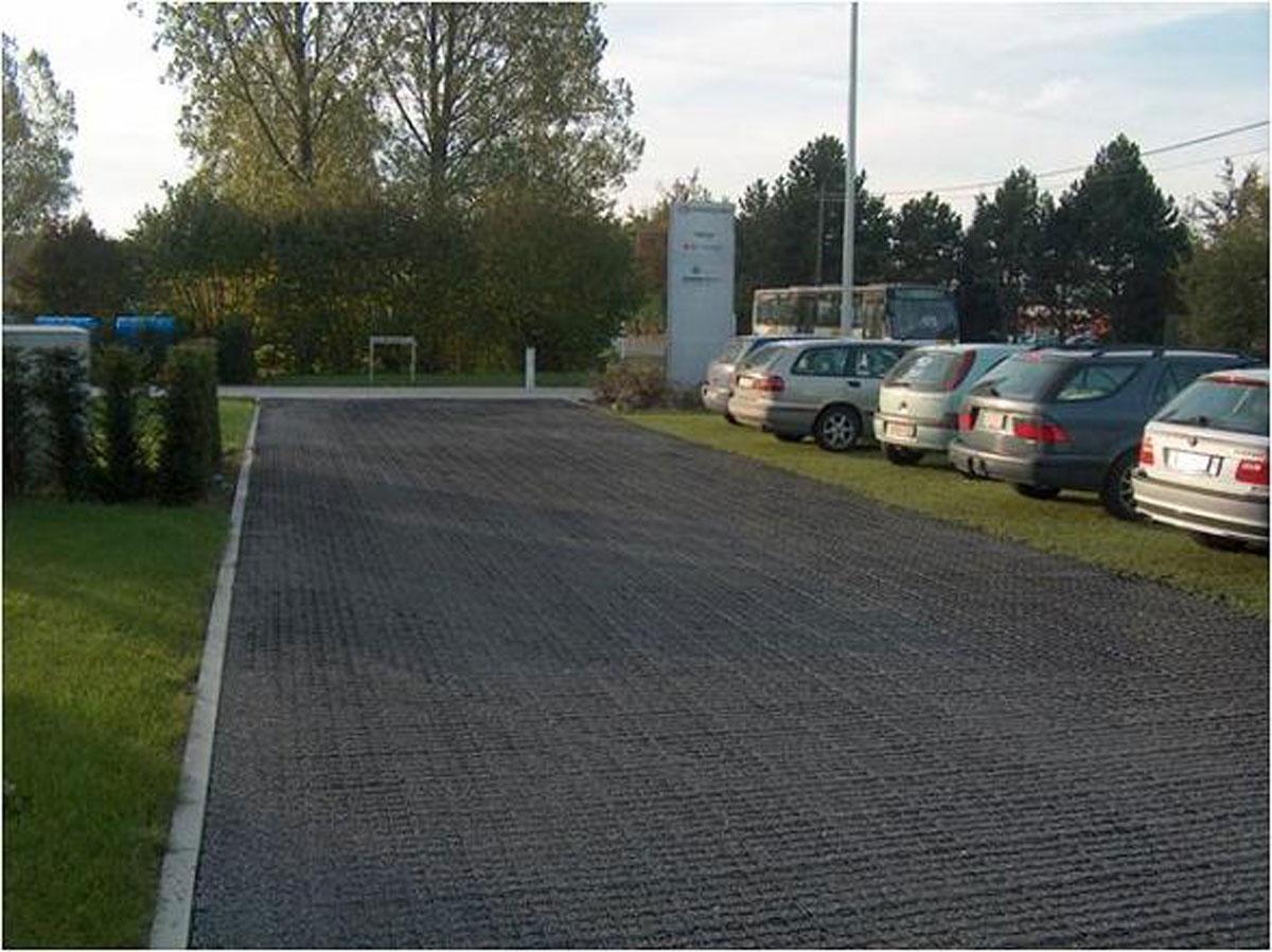 Parking z przepuszczalnymi dla wody kratkami z tworzywa sztucznego - z wypełnionym grysem dojazdem oraz zazielenionymi trawą miejscami postojowymi.